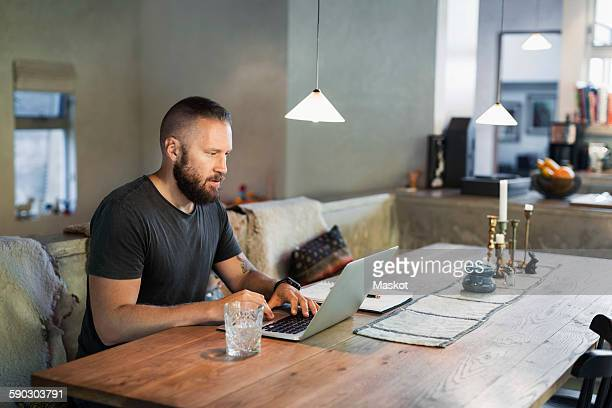 Man working on laptop at dining table in house