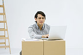 Man working on laptop computer, using cardboard boxes as makeshift desk