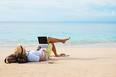 Man working on laptop computer while relaxing on the beach. Idyllic photography covering working anywhere concept.