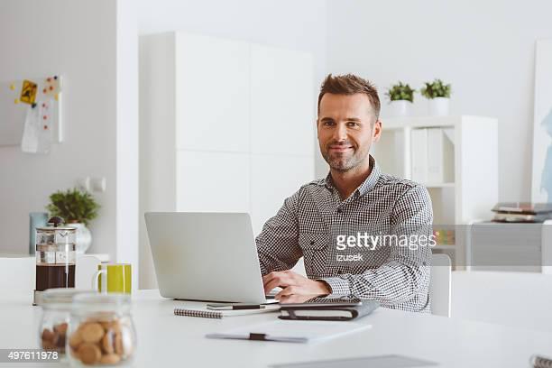 Homme travaillant sur ordinateur portable dans un bureau à domicile