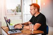 Man in black shirt working on laptop