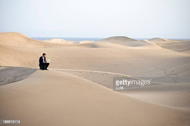 Man working on laptop sitting on a sandy desert hill