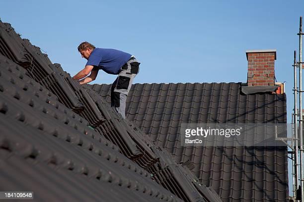 Mann arbeitet auf dem Dach.
