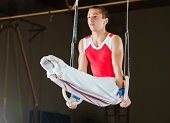 Young man doing difficult exercises on gymnastic rings.