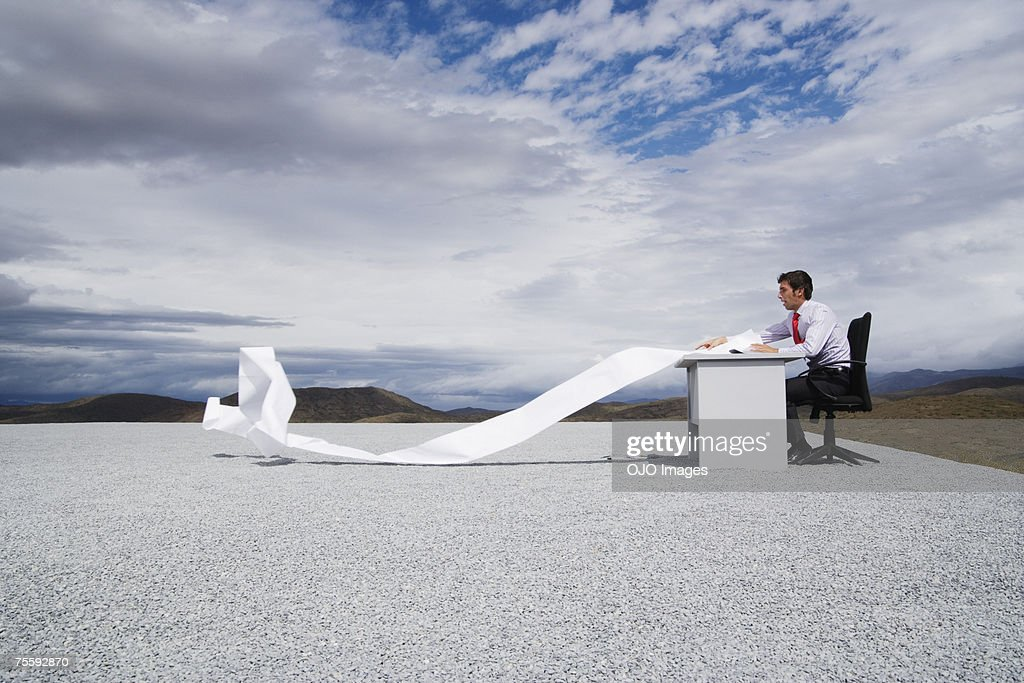 Man working outdoors with papers blowing in the wind : Stock Photo