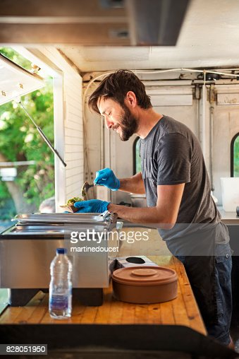 Man working preparing tacos in food truck in a park. : Stock Photo