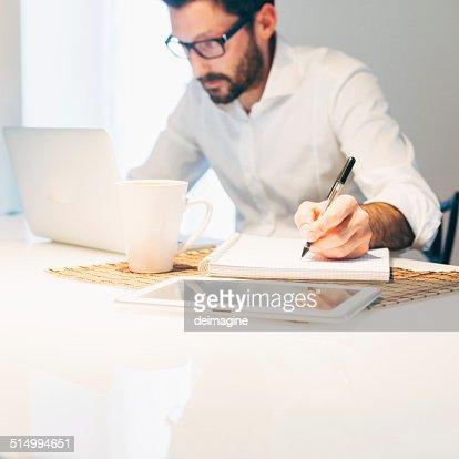 Hombre trabajando con el ordenador portátil en casa