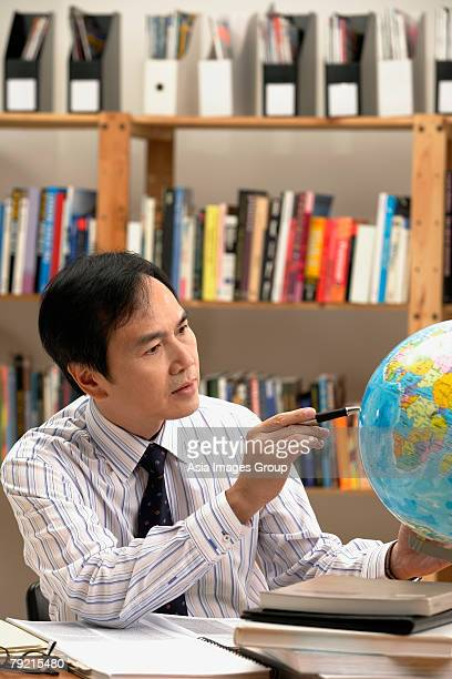 A man working with a globe on the desk