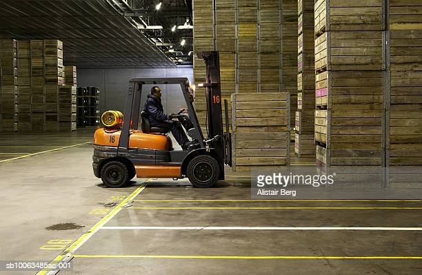 Man working with forklift, lifting crates in workhouse, side view