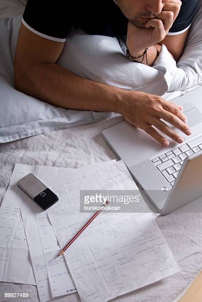 Man working with laptop in bed, close-up, Istanbul, Turkey