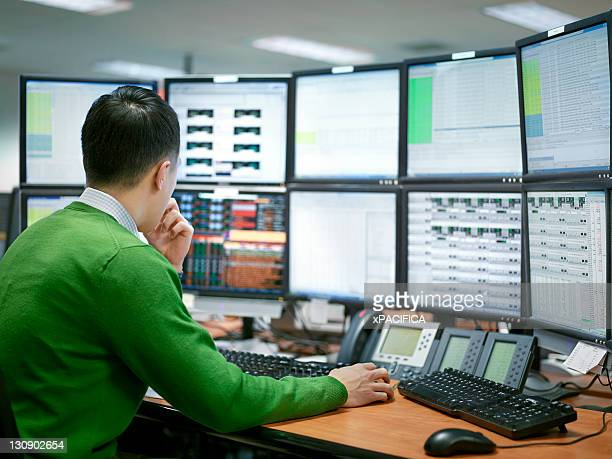 A man working with multiple monitors in an office