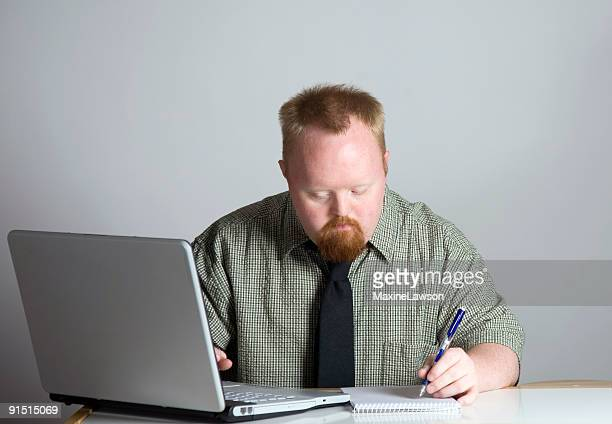 Man working with pencil and paper next to computer