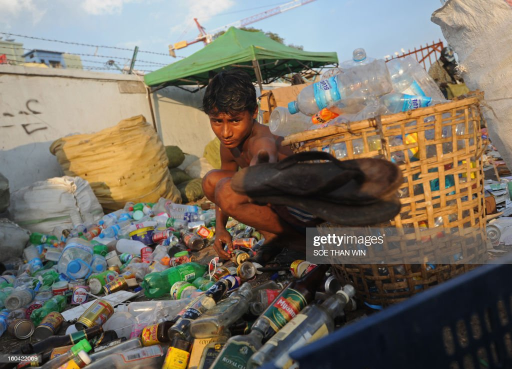 A man works among used bottles he has collected for recycling near a pier in Yangon on January 31, 2013. AFP PHOTO/Soe Than WIN