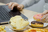 A man works at a computer and eats fast food. unhealthy food: Burger, sauce, potatoes, donuts,chips. Unhealthy concept.