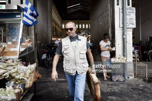 A man works at Athens central food market on July 17 2017 Bolstered by its third bailout programme and positive reports from the European Union...