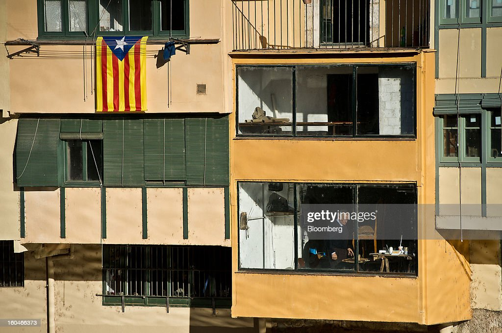 A man works at his furniture restoration workshop beside a pro-independence Catalan flag hanging from the window of a nearby residential building in Girona, Spain, on Thursday, Jan. 31, 2013. Spain's recession deepened more than economists forecast in the fourth quarter as the government's struggle to rein in the euro region's second-largest budget deficit weighed on domestic demand. Photographer: David Ramos/Bloomberg