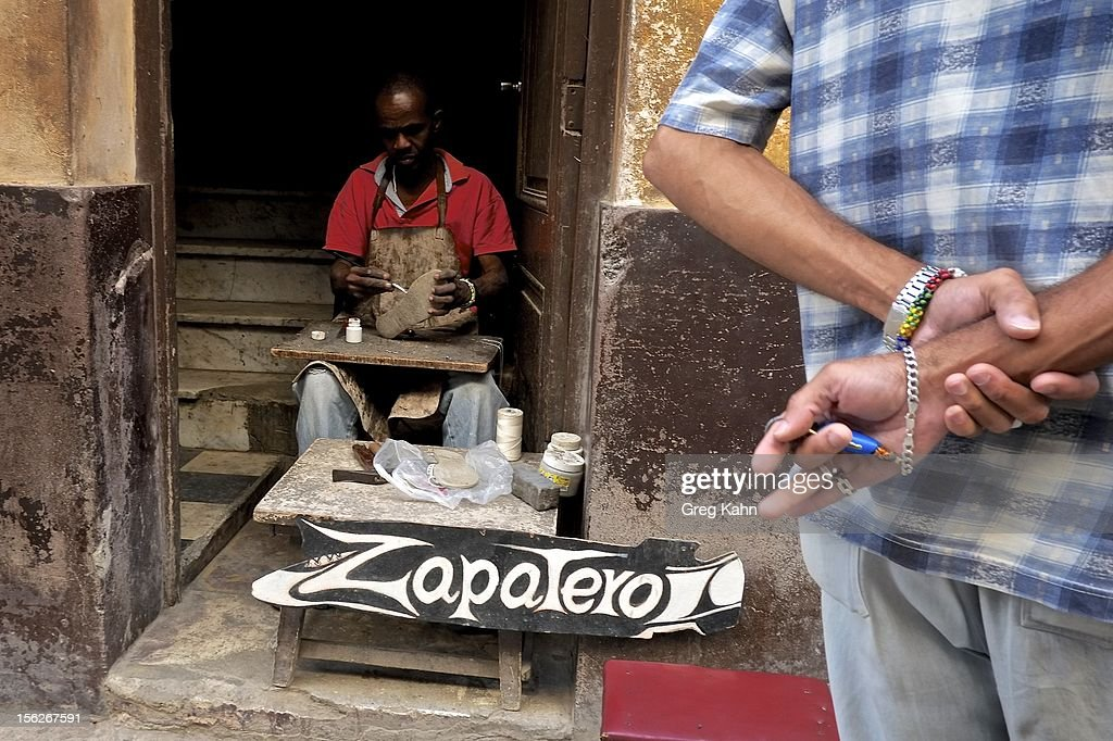 A man works at his shoe repair shop in the doorway of his home November 12, 2012 in Havana, Cuba. New business regulations in the communist country have allowed thousands of citizens to make money for themselves for the first time since 1959.