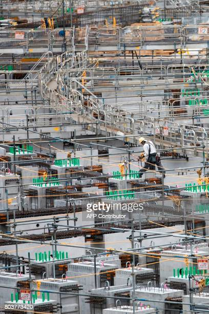 A man works at the construction site for the National Stadium venue for the upcoming Tokyo 2020 Olympics in Tokyo on June 30 2017 The International...