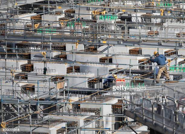 A man works at the construction site for the National Stadium venue for the upcoming Tokyo 2020 Olympic Games in Tokyo on July 21 2017 The suicide of...