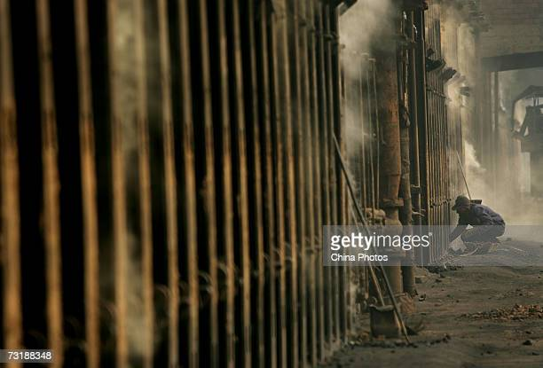 A man works beside the coke furnace at the Xian Coking Factory which will be shut down while the local government launches a campaign to reduce air...