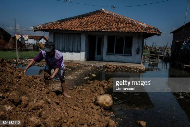 A man works heighten his house at a village surrounded by rising sea levels on June 6 2017 in Pekalongan Indonesia Indonesia is known to be one of...
