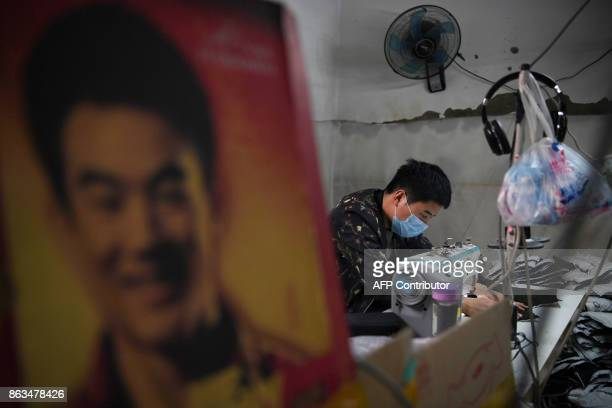 A man works in a clothing factory on the outskirts of Beijing on October 20 2017 China's economy slowed marginally in the third quarter but is well...