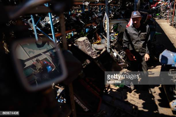 A man works in between stacks of thousands of used engine components at 'The Bike Hospital' on October 18 2017 in Johannesburg South Africa The...