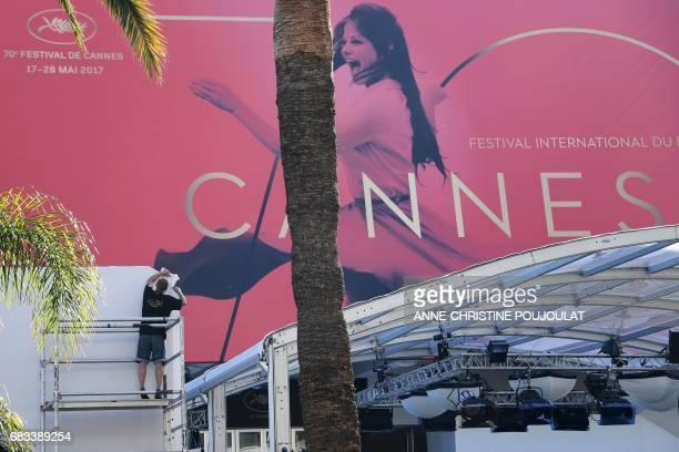 A man works in front of Palais des Festivals under the official poster of the 70th Cannes Film Festival on May 15 2017 on the facade of the Palais...