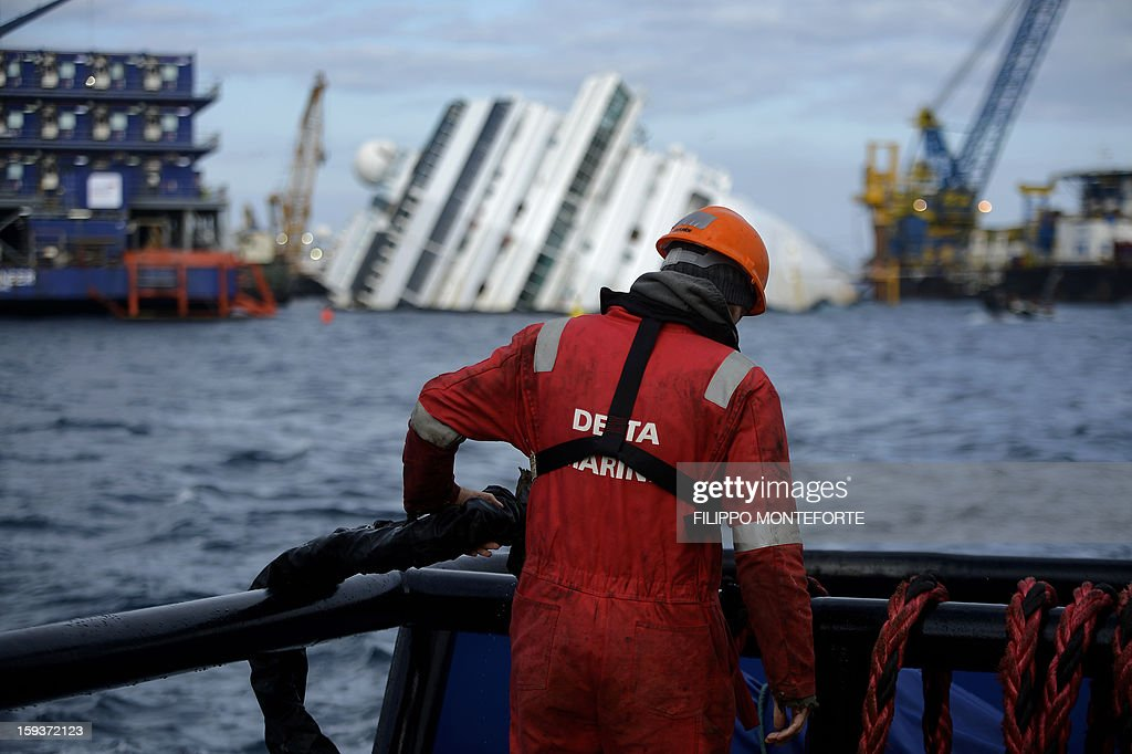 A man works in front of the Costa Concordia cruise ship laying aground outside the port the western Italian island of Giglio on January 12, 2013. On the eve of the first anniversary of the disaster, which claimed 32 lives, the head of Italy's civil protection agency said on January 12 that the wreck would be removed from the island by September at the latest. Four hundred salvage workers have been employed in the removal by a partnership between US salvage giant Titan and Italian salvage company Micoperi.