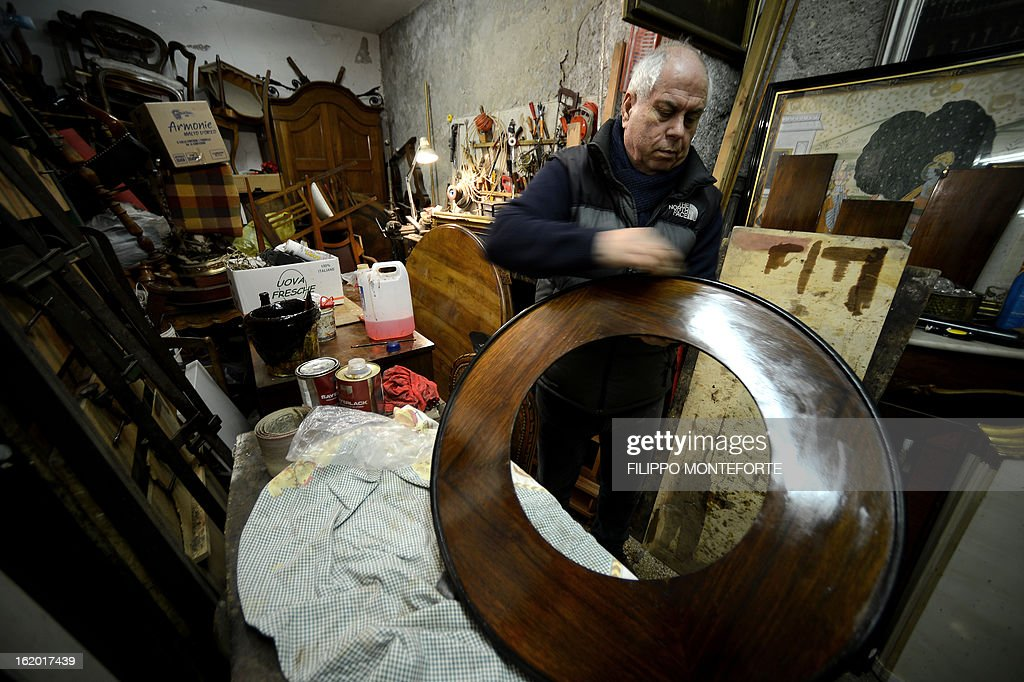A man works in his antiques restoration shop downtown Rome on February 18, 2013. The future of Italy's economy and the social costs of austerity have taken centre stage as Italians prepare to go to the polls next week for an election in which the outcome is far from certain. AFP PHOTO/ Filippo MONTEFORTE