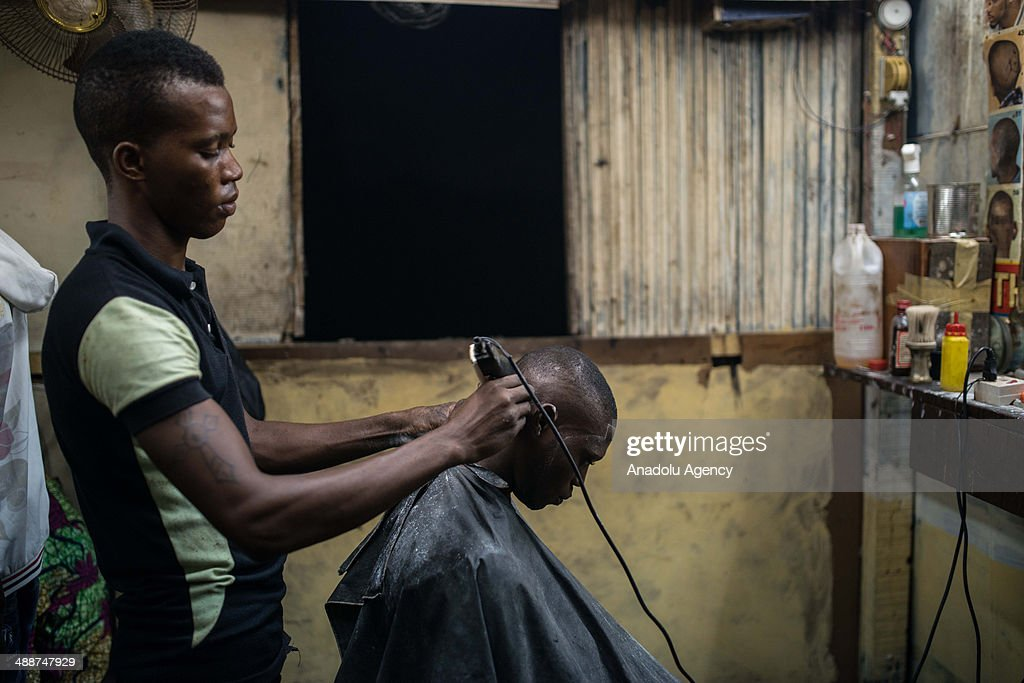 A man works in his hair salon at night on April 30, 2014 in Lagos, Negeria. Makoko is slum neighborhood located in Nigeria, its population considered to be thousands moreover the area was not officially counted. Makoko slum is seldom visited by anyone from outside.
