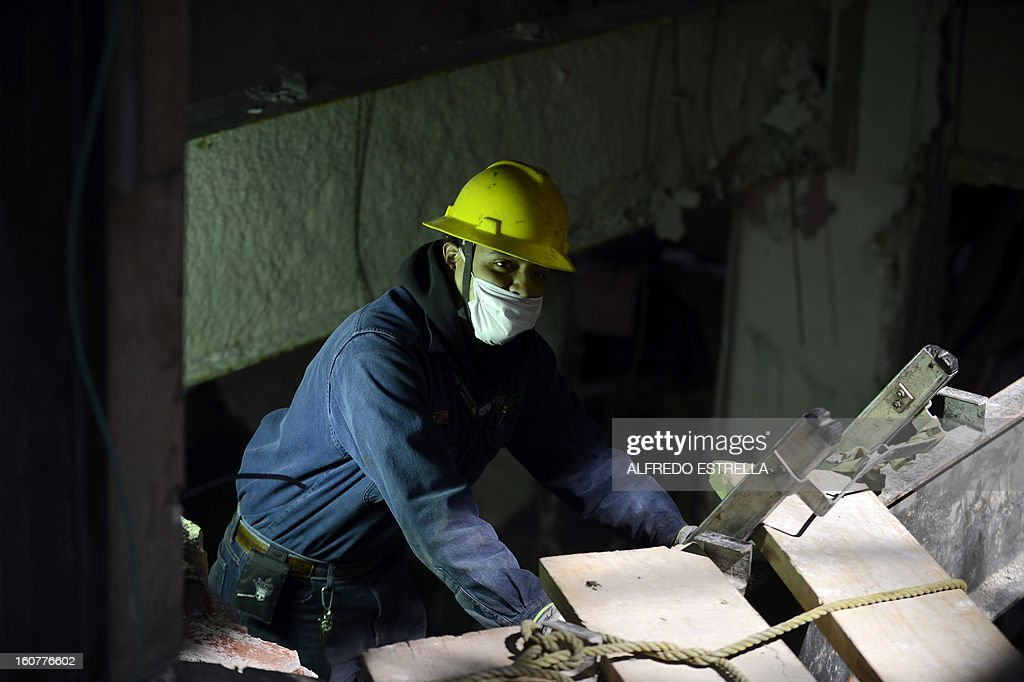A man works in the damaged building of Mexican state-owned oil giant Pemex, after a blast, in Mexico City on February 5, 2013. A gas build-up caused the explosion that rocked the headquarters of Mexico's state-owned oil firm last week, killing 37 people, officials said Monday, ruling out a bomb attack. The explosion also injured morfe than 120 people. AFP PHOTO/Alredo Estrella