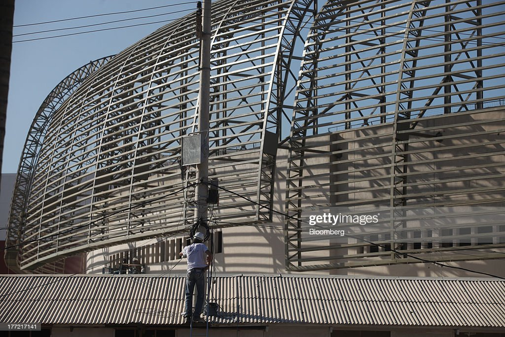 A man works near the Metropolitano Barra Shopping center under construction in Rio de Janeiro, Brazil, on Wednesday, Aug. 21, 2013. Latin America's largest economy created 7,154 manufacturing jobs and 4,899 construction jobs in July, down from 24,718 and 25,433 new posts a year ago. Photographer: Dado Galdieri/Bloomberg via Getty Images