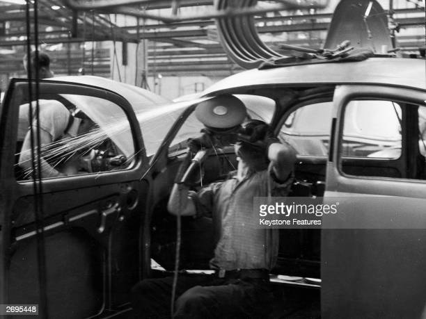 A man works on a car production line in a Volkswagen factory in Wolfsburg West Germany