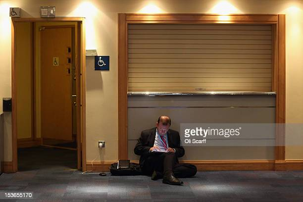 A man works on a computer outside a toilet at the Conservative party conference in the International Convention Centre on October 8 2012 in...