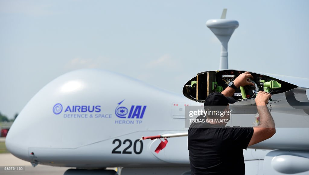 A man works on a 'Heron' drone at the International Aerospace Exhibition (ILA) in Schoenefeld near Berlin on May 30, 2016. The Aerospace Exhibition at Schoenefeld Airport takes place from June 1 to 4, 2016. / AFP / TOBIAS