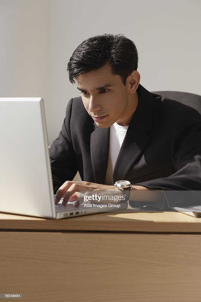 A man works on a laptop : Stock Photo