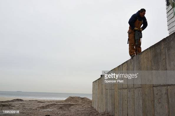 A man works on a protective wall near homes damaged by Hurricane Sandy along the beach in the Rockaways on January 15 2013 in the Queens borough of...