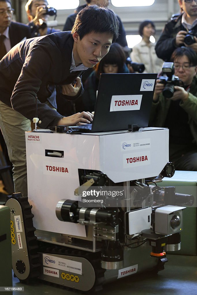 A man works on a remote-controlled amphibious monitoring device for measuring pollution levels in air and water, developed by Toshiba Corp. in the New Energy and Industrial Technology Development Organization's (NEDO) unmanned anti-disaster system research and development project, during a demonstration at Chiba Institute of Technology's (CIT) Shibazono campus in Narashino City, Chiba Prefecture, Japan, on Wednesday, Feb. 20, 2013. NEDO, Japan's largest public R&D management organization, introduced its latest disaster response robots technologies today. Photographer: Kiyoshi Ota/Bloomberg via Getty Images