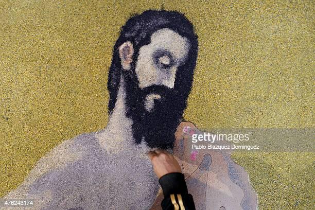 A man works on a sawdust carpet depicting 'Jesus' along the streets during the Corpus Christi feast on June 7 2015 in Elche de la Sierra near...