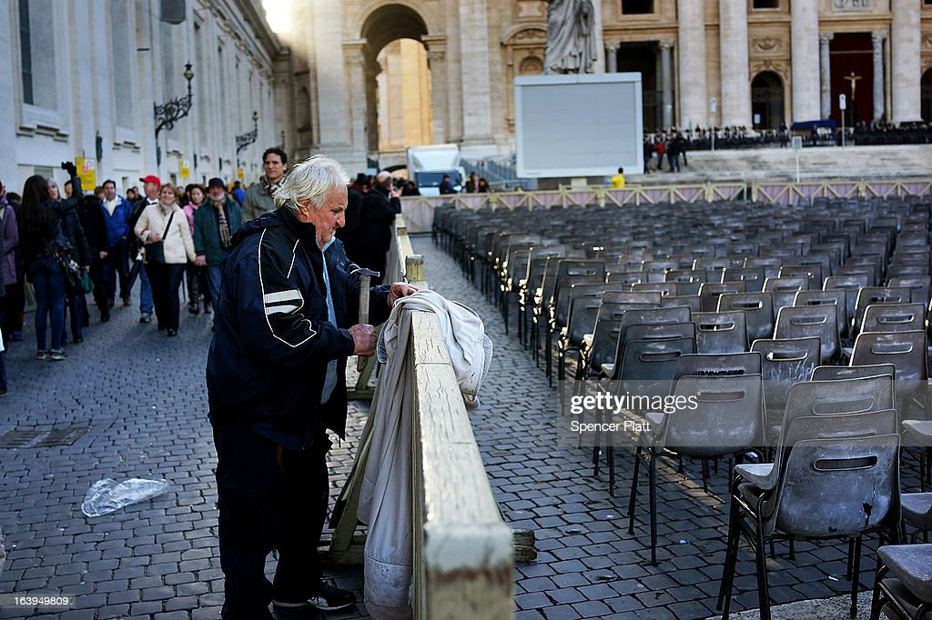 A man works on a security barrier Chairs in front of St Peter's Basilica as workers prepare for the inauguration mass of Pope Francis on March 18, 2013 in Vatican City, Vatican. The Inauguration Mass for Pope Francis will take place on March 19, the feast day for St. Joseph.