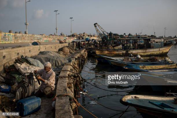 A man works on an engine at the Gaza port on July 22 2017 in Gaza City Gaza Gaza's fishermen suffer under the blockade and are only permitted to go...
