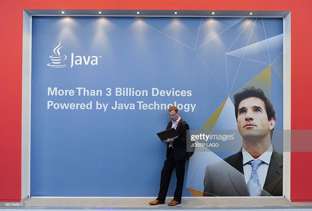 A man works on his laptop in front of a board of Java at the 2013 Mobile World Congress in Barcelona on February 27, 2013. The 2013 Mobile World Congress, the world's biggest mobile fair, is held from February 25 to 28 in Barcelona. AFP PHOTO / JOSEP LAGO