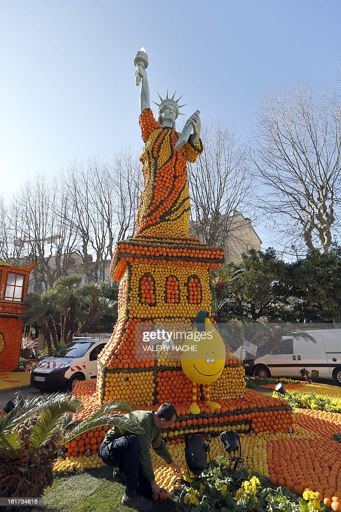 A man works on 'La statue de la Liberte' a sculpture made of oranges and lemons, on February 15, 2013 in Menton on the French Riviera, ahead of the start of the 'Fete du Citron' (lemon carnival). The theme of this 80th edition, running from February 16 until March 6, 2013, is 'Le Tour du monde en 80 jours' (80 days around the world). AFP PHOTO / VALERY HACHE