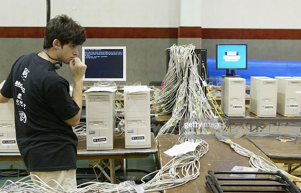 A man works on setting up a computer for Flashmob 1, the first flashmob supercomputer April 3, 2004 at the University of San Francisco in San Francisco, California. Hundreds of computer enthusiasts connected hundreds of computers via high-speed LAN to work together as a single supercomputer in hopes to place in the top 500 fastest supercomputers on earth.