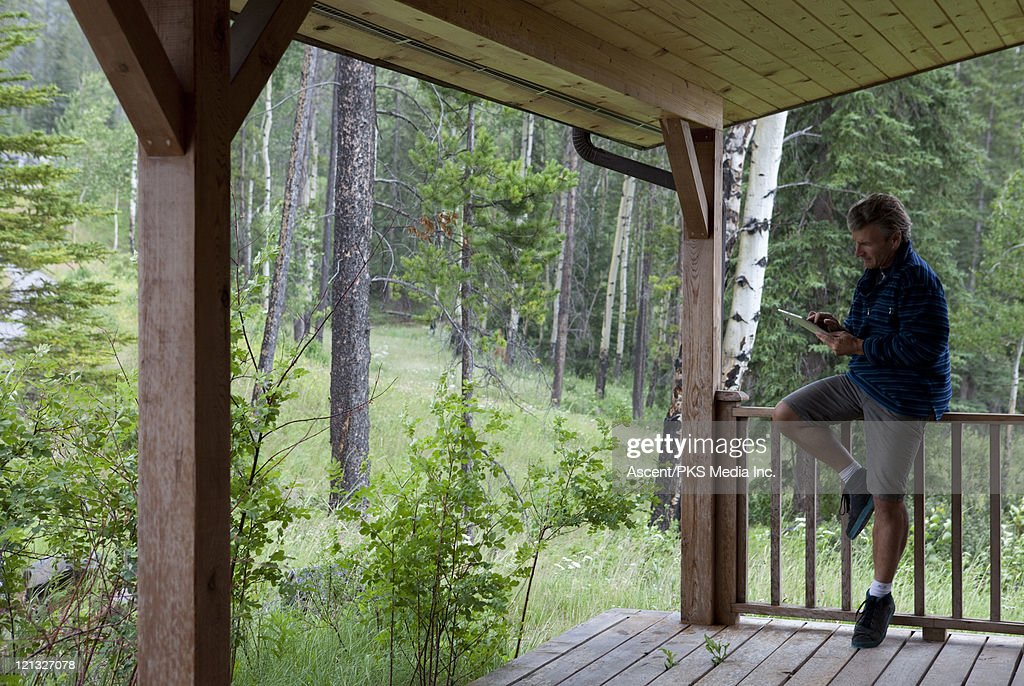 Man works on tablet from wooden deck, in forest : Stock Photo