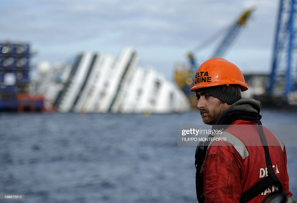 A man works on the Costa Concordia cruise ship laying aground outside the port the western Italian island of Giglio on January 12, 2013. A year after the Costa Concordia tragedy in which 32 people lost their lives, the giant cruise ship still lies keeled over on an Italian island and its captain Francesco Schettino has become a global figure of mockery. AFP PHOTO / FILIPPO MONTEFORTE