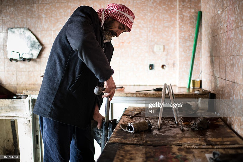 A man works on the production of hand made missiles in a secret factory on January 19, 2013 in Al-Bab, 30 kilometers from the northeastern Syrian city of Aleppo. Recycled or non explosed bombs recolted after shellings are used for the manufacturing and sugar as well for the propulsion. Each day, nearly 50 missiles are assembled for the Abu baker Brigade.