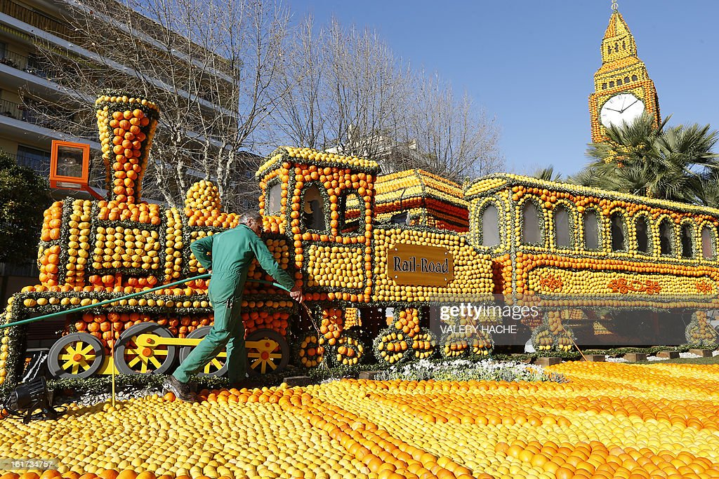 A man works on 'The rail road with Big Ben' a sculpture made of oranges and lemons, on February 15, 2013 in Menton on the French Riviera, ahead of the start of the 'Fete du Citron' (lemon carnival). The theme of this 80th edition, running from February 16 until March 6, 2013, is 'Le Tour du monde en 80 jours' (80 days around the world). AFP PHOTO / VALERY HACHE