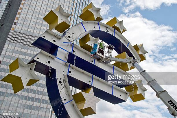 A man works on the sculpture by German artist Ottmar Hoerl depicting the Euro logo in front of the former headquarters of the European Central Bank...